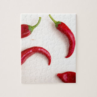 Hot chili peppers on a light wooden board puzzles
