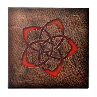 Hot orange celtic flower on leather tile