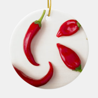 Hot red chili peppers on a light wooden board ceramic ornament