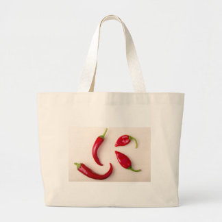 Hot red chili peppers on a light wooden board large tote bag