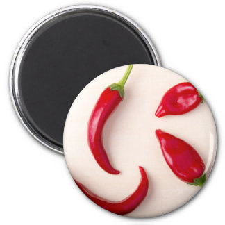 Hot red chili peppers on a light wooden board magnet