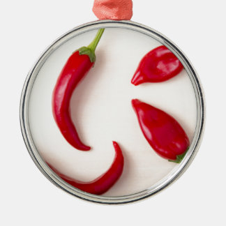 Hot red chili peppers on a light wooden board metal ornament