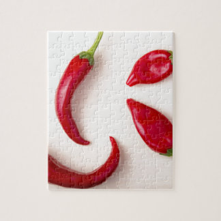 Hot red chili peppers on a light wooden board puzzles