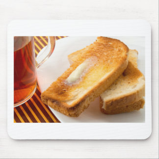 Hot toast with butter on a white plate close-up mouse pad