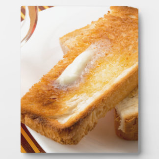 Hot toast with butter on a white plate close-up plaque