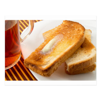 Hot toast with butter on a white plate close-up postcard