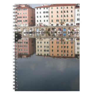 Houses and boats are reflected in the water notebook