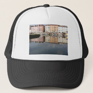 Houses and boats are reflected in the water trucker hat
