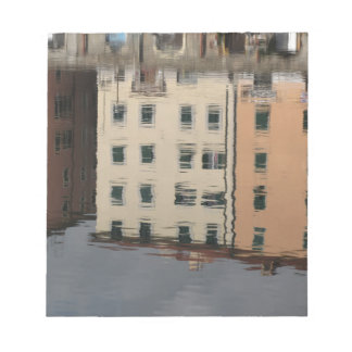 Houses are reflected in the tranquil water notepad