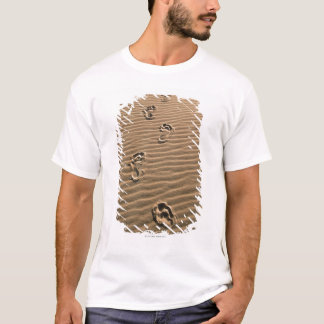 Human footprints on sandy beach T-Shirt