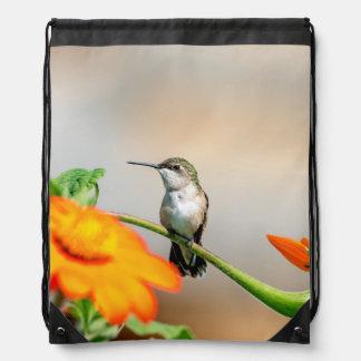 Hummingbird on a flowering plant drawstring bag
