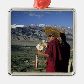 India, Ladakh, Thikse. Buddhist monk blows Metal Ornament