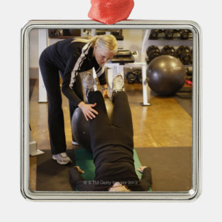 Instructor helps senior client with stretches christmas tree ornament