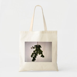 Isolated dark green leaves branch tote bags