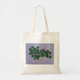 Isolated green branch with leaves on a concrete fl tote bags