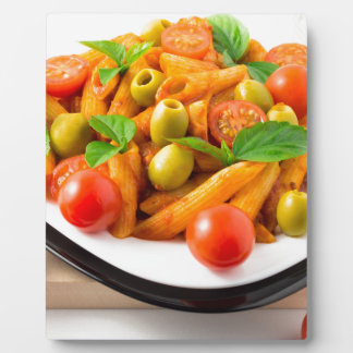 Italian pasta penne in tomato sauce with olives plaque