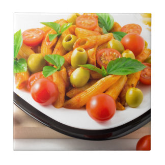 Italian pasta penne in tomato sauce with olives tile