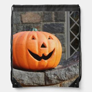 Jack-o-lantern on a stone wall backpacks