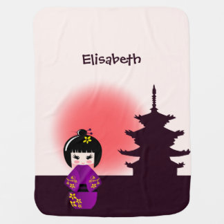 Japanese kokeshi doll at temple name baby girl receiving blanket