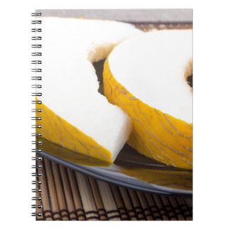 Juicy yellow melon on wooden background note books