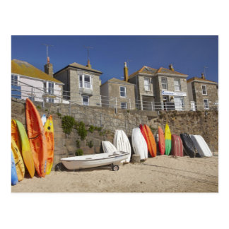 Kayaks and dinghies stacked against seawall at postcard