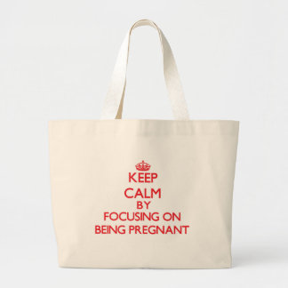 Keep Calm by focusing on Being Pregnant Canvas Bags