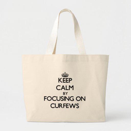 Keep Calm by focusing on Curfews Tote Bags