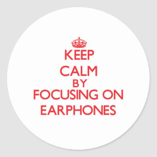 Keep Calm by focusing on EARPHONES Round Sticker