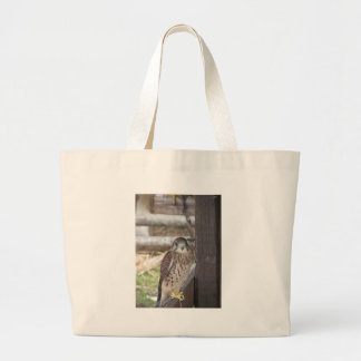 Kestrel perched on a fence post large tote bag