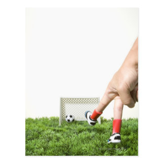Kicking a soccer ball with finger imitating postcard