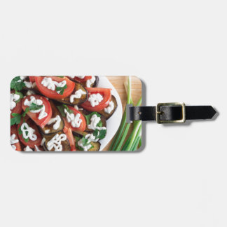 Kitchen table with a dish of stewed eggplant luggage tag