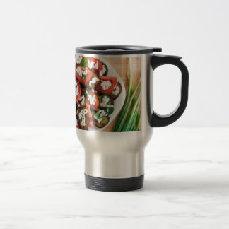 Kitchen table with a dish of stewed eggplant travel mug