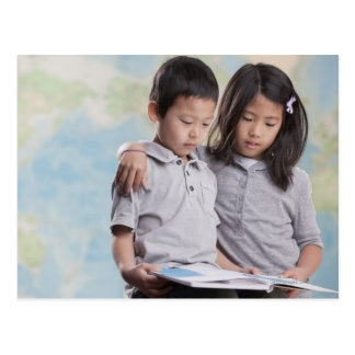 Korean children reading book near map postcard
