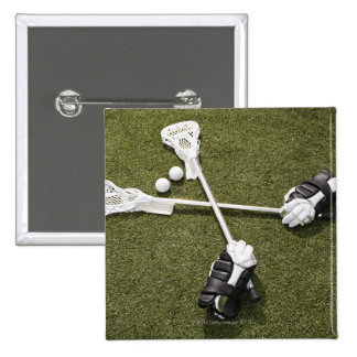 Lacrosse sticks, gloves and balls on artificial 15 cm square badge