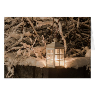 Lantern with a candle in the middle of snow greeting card