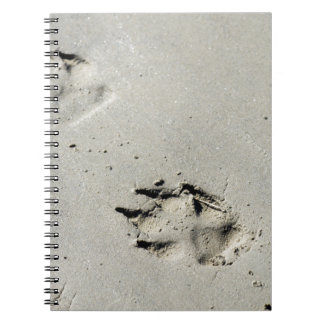 Large dog's paw prints on wet sand notebook