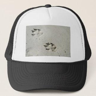 Large dog's paw prints on wet sand trucker hat
