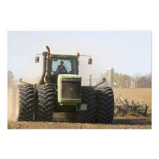 Large tractor cultivating spring soil on a photograph