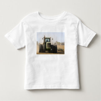 Large tractor cultivating spring soil on a shirt