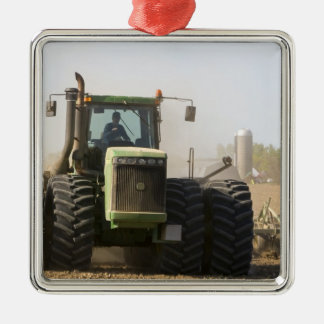 Large tractor cultivating spring soil on a Silver-Colored square decoration
