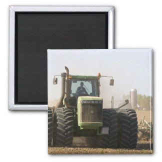 Large tractor cultivating spring soil on a square magnet