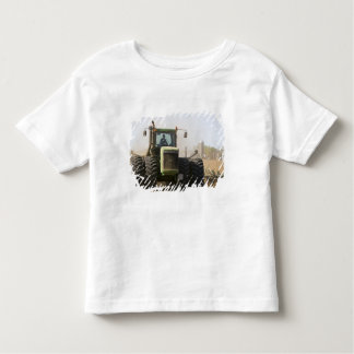 Large tractor cultivating spring soil on a t shirt