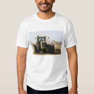Large tractor cultivating spring soil on a tee shirts