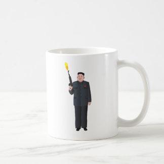 Laughing Kim Jong-un firing a gun into the air Coffee Mug