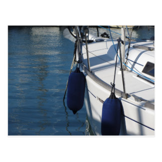 Left side of sailing boat with two blue fenders postcard