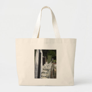 Line of closed beach chairs and umbrellas large tote bag