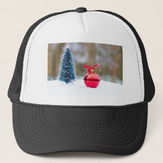 Little christmas tree and red bauble in snow trucker hat