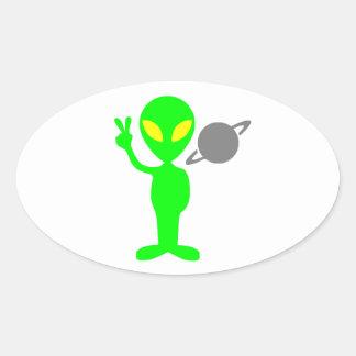 Little Green Alien Next to the Planet Saturn Oval Sticker