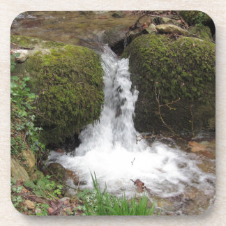 Little waterfall by mossy rocks in the forest coaster