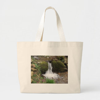 Little waterfall by mossy rocks in the forest large tote bag